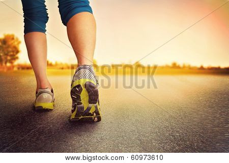 an athletic pair of legs on pavement during sunrise or sunset - healthy lifestyle concept