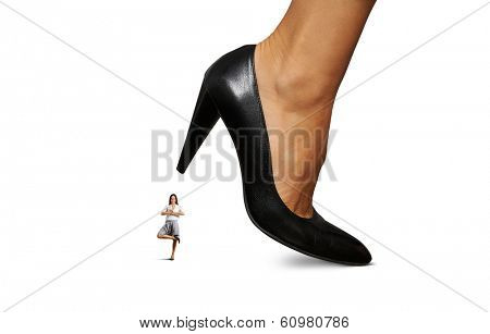 calm smiley businesswoman under big heel. isolated on white background