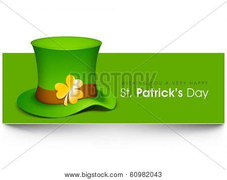 Happy St. Patrick's Day celebrations concept with leprechauns hat decorated by gold shamrock leaf on grey and green background.