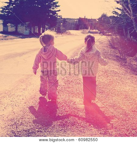 Two girls holding hands walking on road - instagram effect