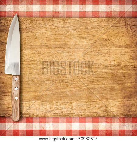 Cutting breadboard and knife over red grunge gingham tablecloth background