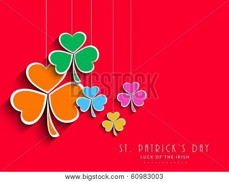 Colourful hanging clover leaves on red background, can be use as sticker, tag or label for Happy St. Patrick's Day celebrations.