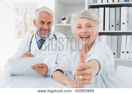 Portrait of a happy senior patient gesturing thumbs up with doctor at the medical office