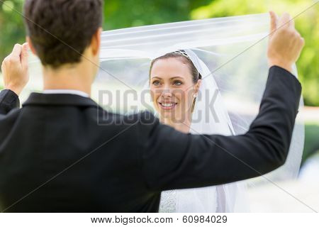 Young groom unveiling his bride in garden