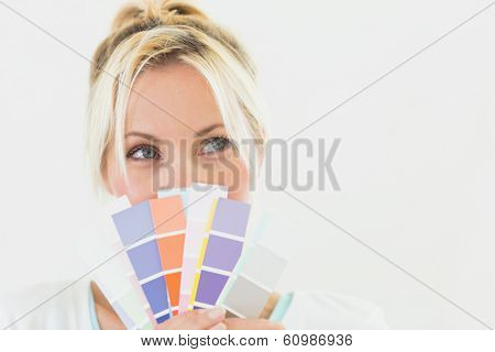 Closeup of a beautiful young woman holding color swatches over white background