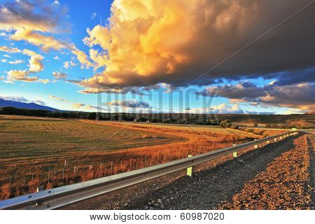 In the steppe runs a gravel road. Storm over the Pampas. The enormous storm cloud and a flat plain covered in orange sunset.