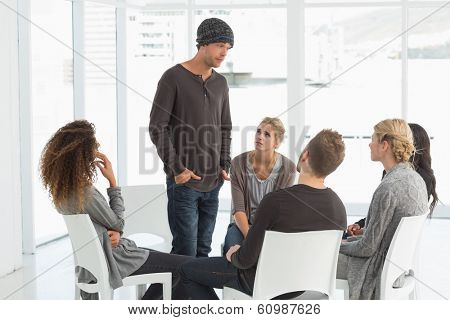 Rehab group listening to man standing up introducing himself at therapy session
