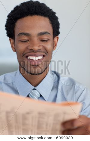 Smiling Afro-american Businessman Reading A Newspaper