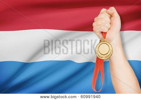 Medal In Hand With Flag On Background - Grand Duchy Of Luxembourg