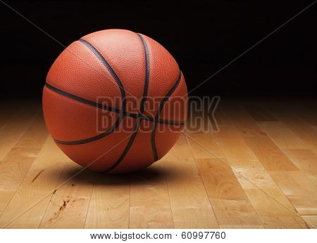 Basketball With Dark Background On A Wood Gym Floor