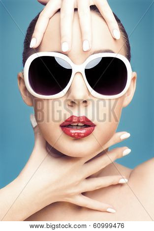 close up studio portrait of young beautiful woman wearing white sunglasses