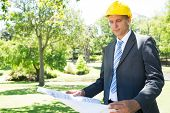 stock photo of half-dressed  - Well dressed businessman studying blueprint in park - JPG