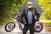 stock photo of chopper  - Mature biker in leather jacket standing in front of his chopper on an open road - JPG