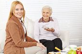 Senior woman and caregiver eating breakfast together at home