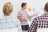 stock photo of presenter  - Smiling young designer presenting ideas to colleagues in creative office - JPG
