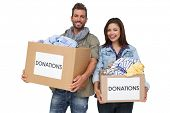 Portrait of a happy young couple with clothes donation standing over white background