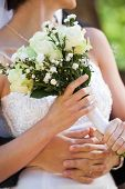 Close-up mid section of a young newlywed couple with bouquet in the park