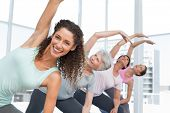 stock photo of senior class  - Happy female trainer with class stretching hands at yoga class - JPG