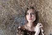 stock photo of scythe  - beautiful girl with a scythe in a brown dress on a gray background - JPG