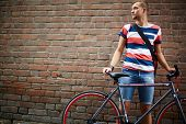 Portrait of calm guy with bicycle standing against brick wall