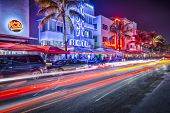 MIAMI, FLORIDA - JANUARY 6, 2014: Cars speed down Ocean Drive. The road is the main thoroughfare thr