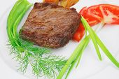 meat savory : grilled beef fillet mignon on white plate with tomatoes apples and pepper isolated ove