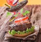 stock photo of hamburger-steak  - Delicious hamburger on wooden background - JPG