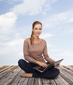 happiness, internet, technology and people concept - smiling young woman sitting on floor with lapto
