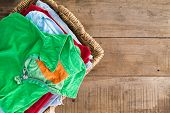 picture of wooden basket  - Clean washed unironed summer clothes with a fresh fragrance stacked in a wicker laundry basket with a bright green shirt on top overhead view on rustic wooden boards with copyspace to the right - JPG