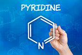 Hand with pen drawing the chemical formula of pyridine