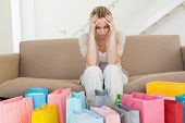 Regretful woman looking at many shopping bags on the couch at home in the living room