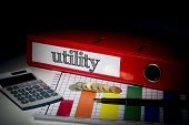 The word utility on red business binder on a desk