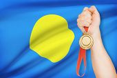 Medal In Hand With Flag On Background - Republic Of Palau