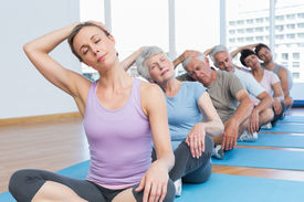pic of senior class  - Female trainer with class stretching neck in row at yoga class - JPG