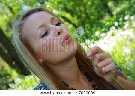 The girl the blonde holds a dandelion