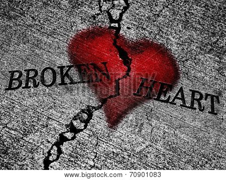 Large crack in cement with words broken heart and red