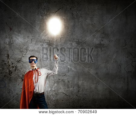 Young confident superman in mask and cape