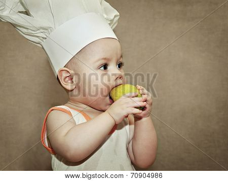 Little Baby In A Chef's Hat Eating A Pear