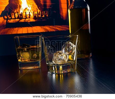 Glasses Of Whiskey With Ice Cubes Near Whiskey Bottle In Front Of The Fireplace