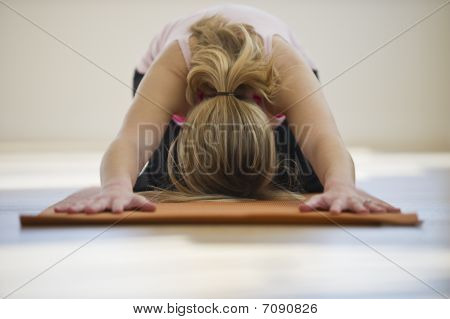 Woman Doing Yoga On Mat In Studio