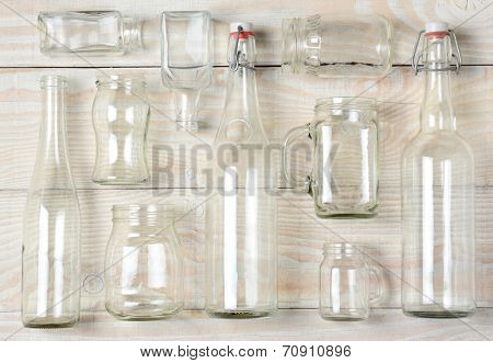 High angle shot of assorted glass bottles on a whitewashed wooden table. Clear glass bottles and containers of various sizes and shapes, horizontal format.
