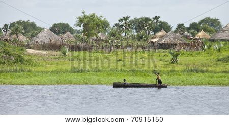 PANWEL, SOUTH SUDAN- JUNE 23 2012: Unidentified children canoe past their village on the Nile in South Sudan
