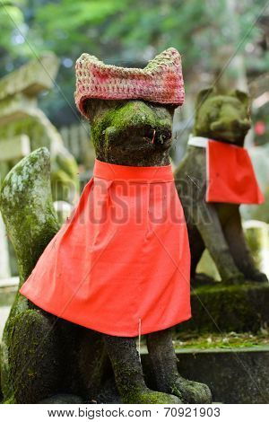 Stone fox (Inari messenger of God) statue with red cap at the Fushimi-Inari Taisha, Kyoto, Japan