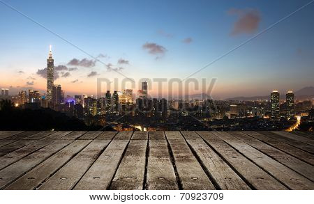 City skyline in night with famous 101 skyscraper and buildings in Taipei, Taiwan. Focus on wooden floor.