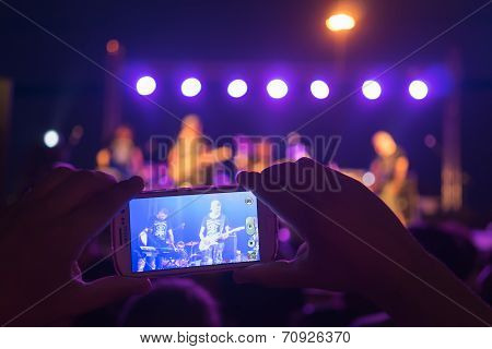 Fan Watches Band Blue Feathers Performing Live Through His Mobile Phone In Thessaloniki, Greece.