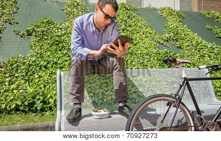 Young business man working with electronic tablet in lunch break