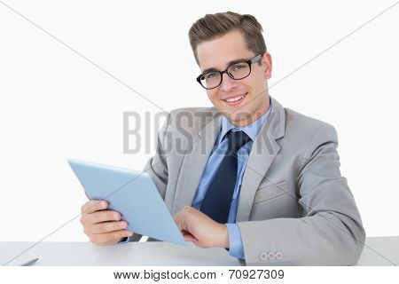 Nerdy businessman working on tablet pc on white background