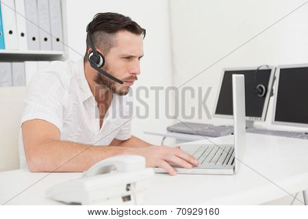 Call center agent on a call at his desk in his office