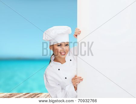 cooking, advertisement and food concept - smiling female chef, cook or baker with white blank board