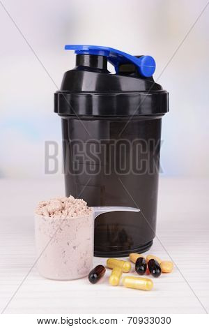 Whey protein powder in scoop with vitamins and plastic shaker on table on bright background